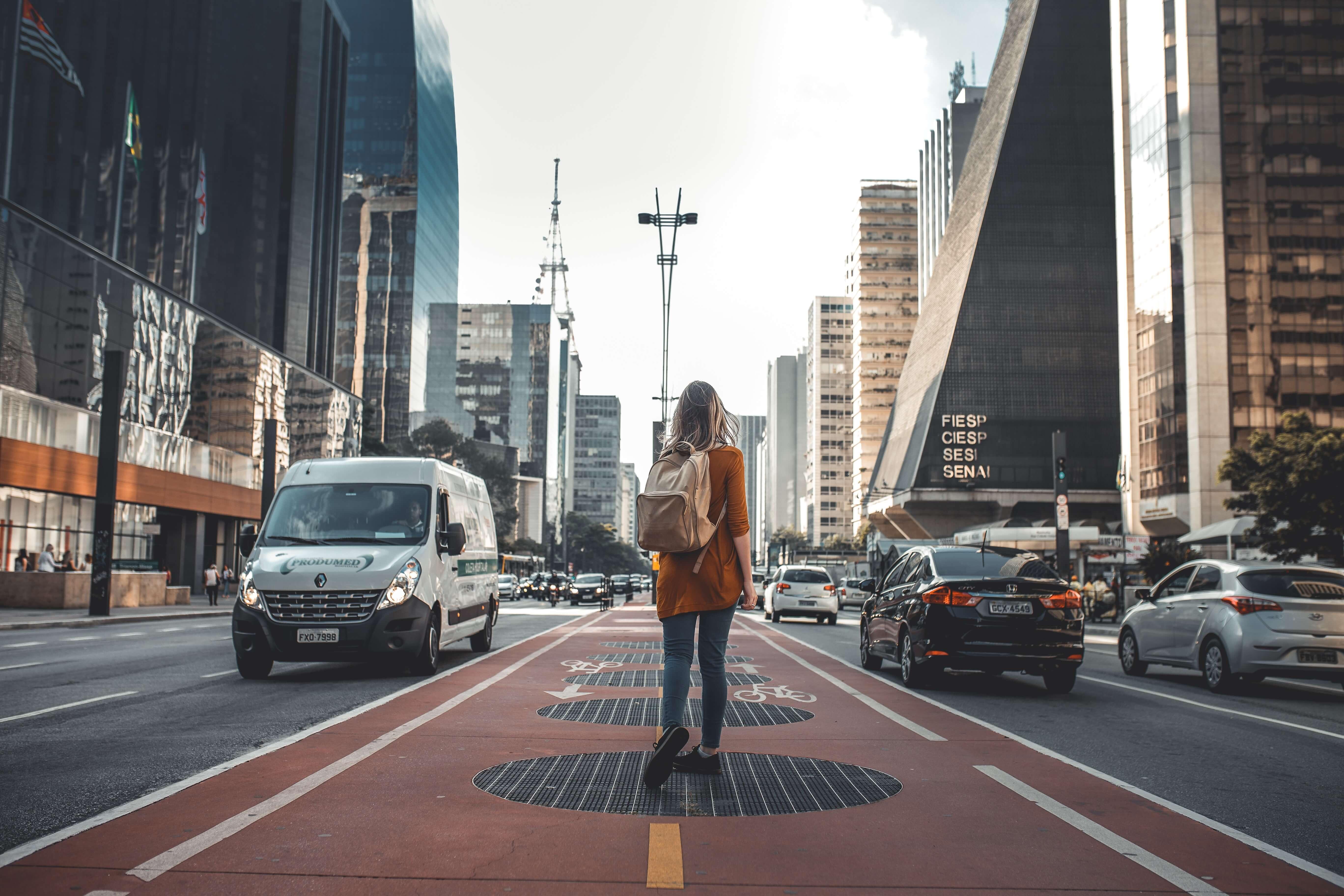 道路の真ん中に立つ女性の後ろ姿