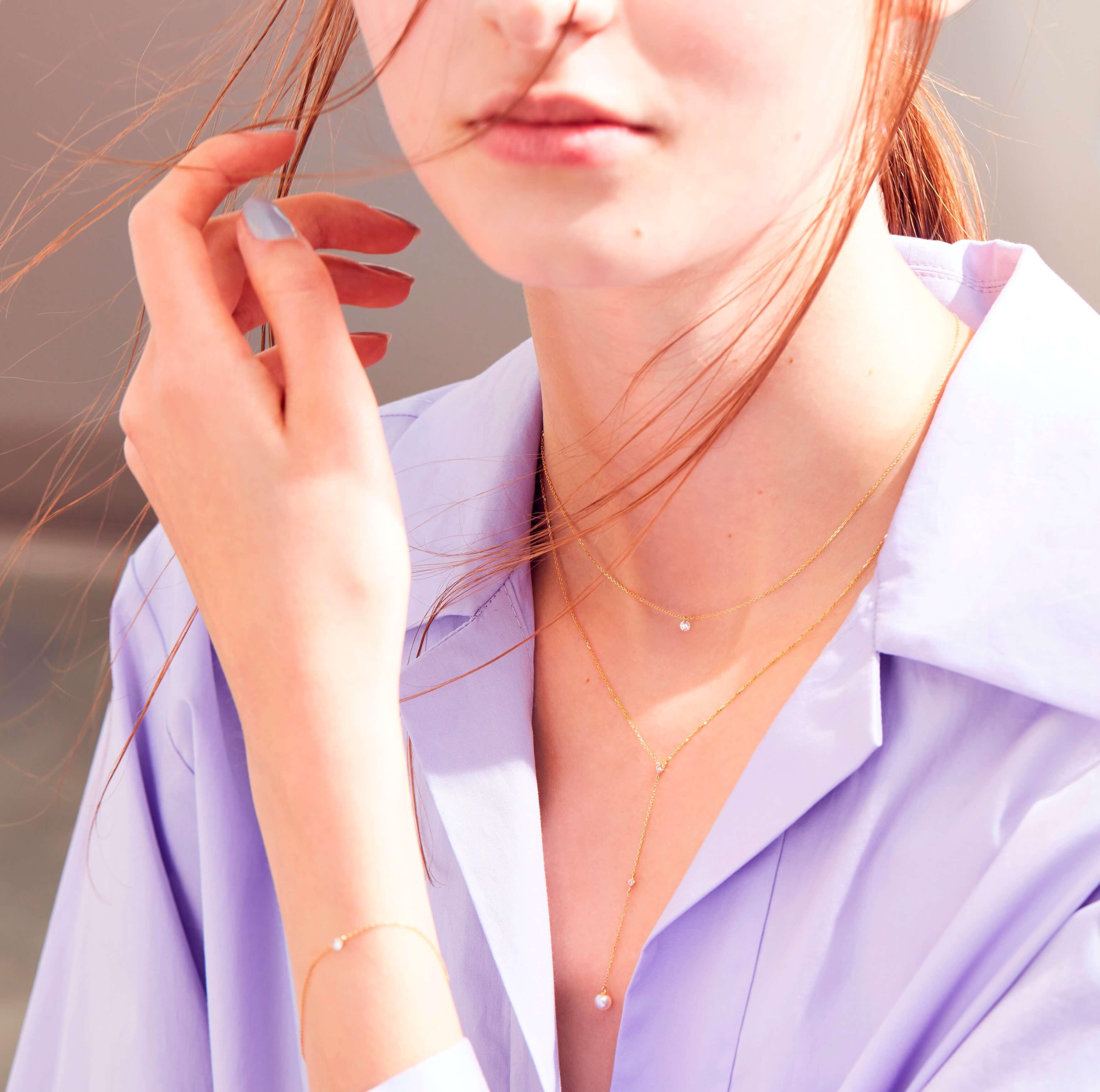 4℃のネックレスを身に着ける女性