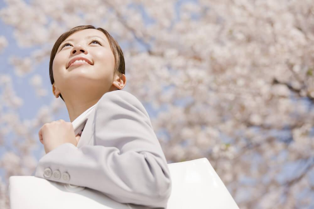 桜の木の下で微笑む新社会人