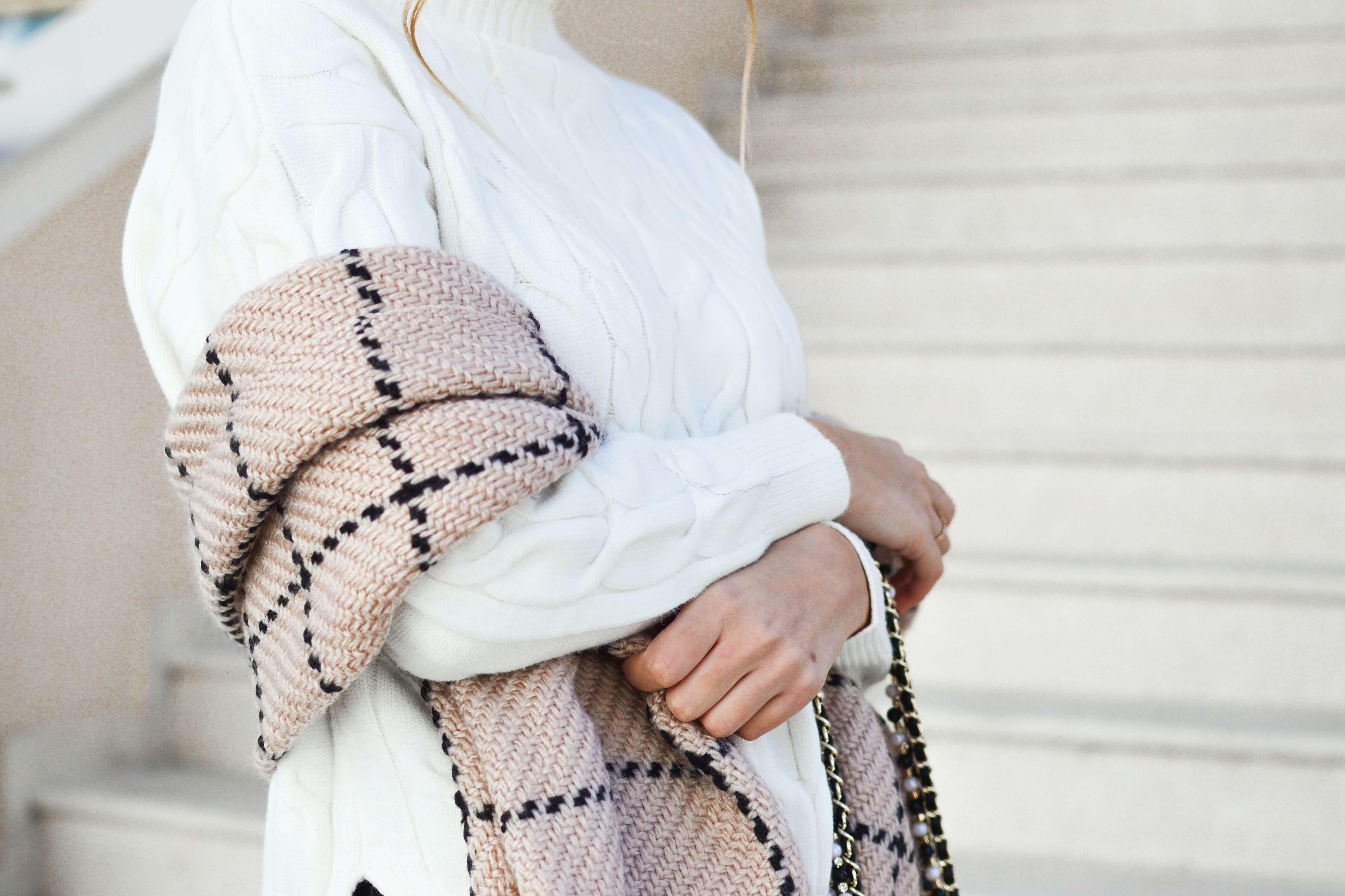 アイボリーのニットワンピースを着た女性