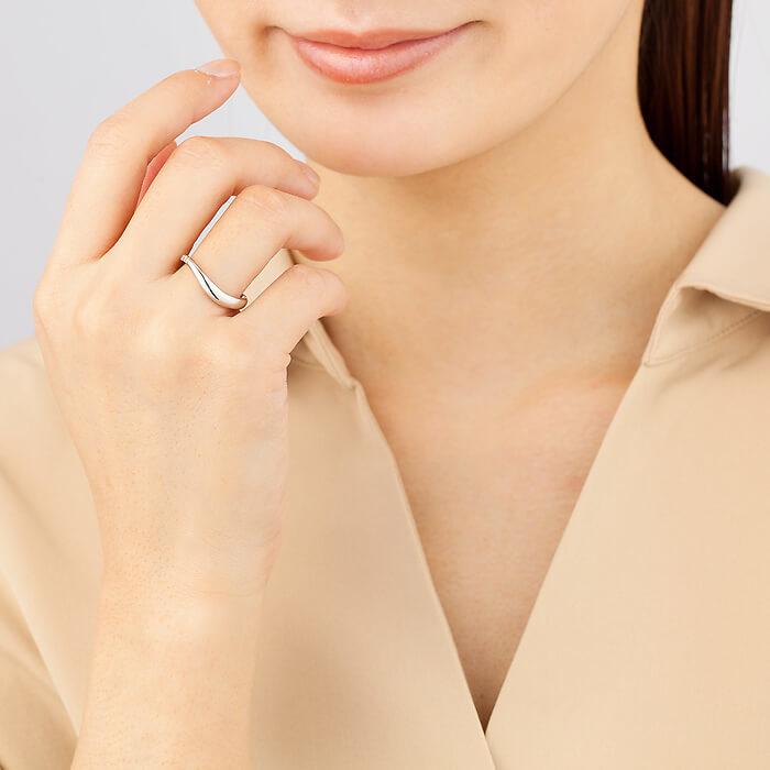 中指にシルバーリングをつけた女性