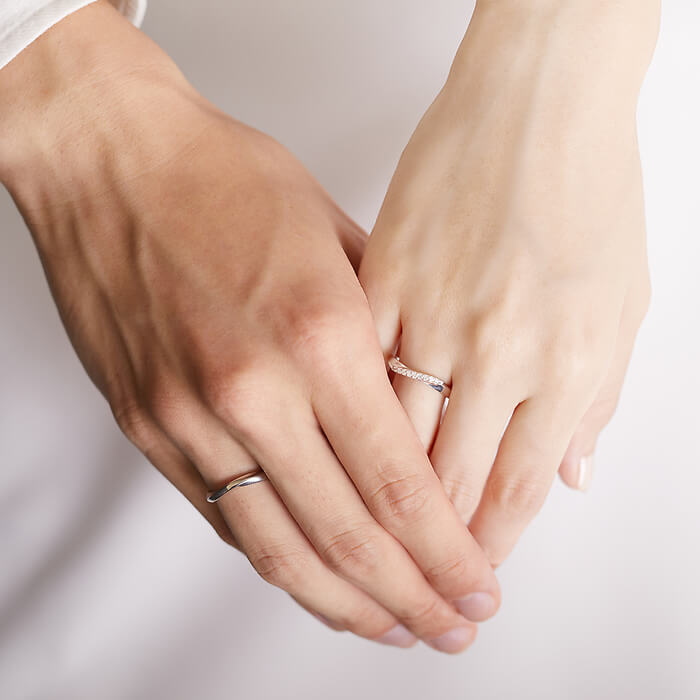 シルバーのペアリングをつけた手をつなぐカップル