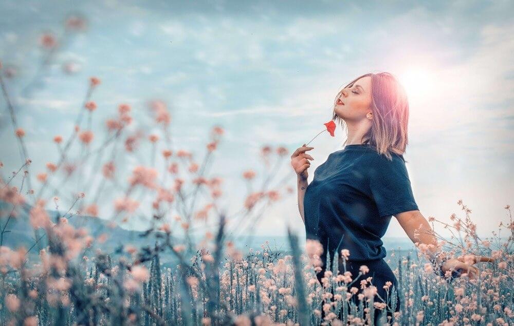 花畑に佇むTシャツを着た女性