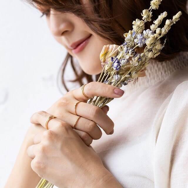 花をもって指輪をつけた女性