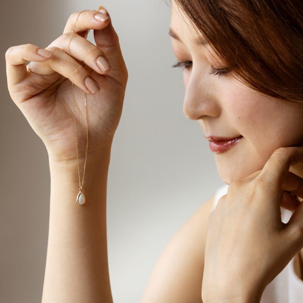 4℃のネックレスを持つ女性