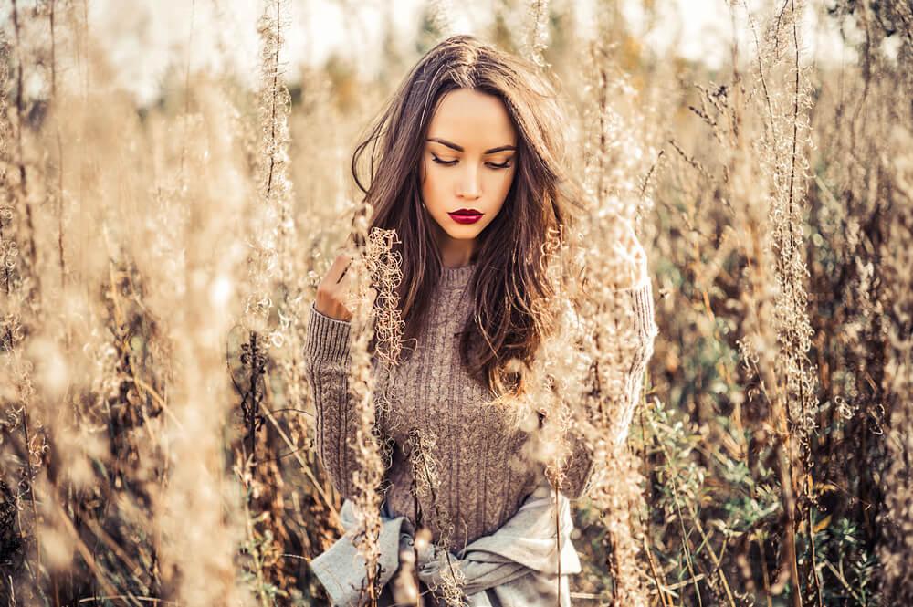 秋の植物の中で立つ女性