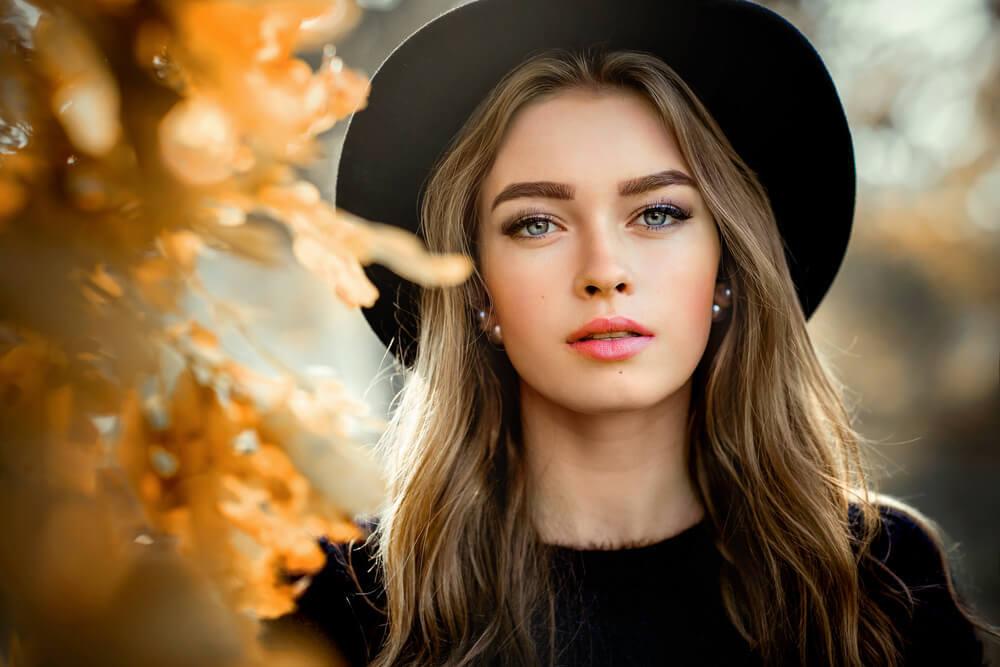 秋の景色の中に立つ女性