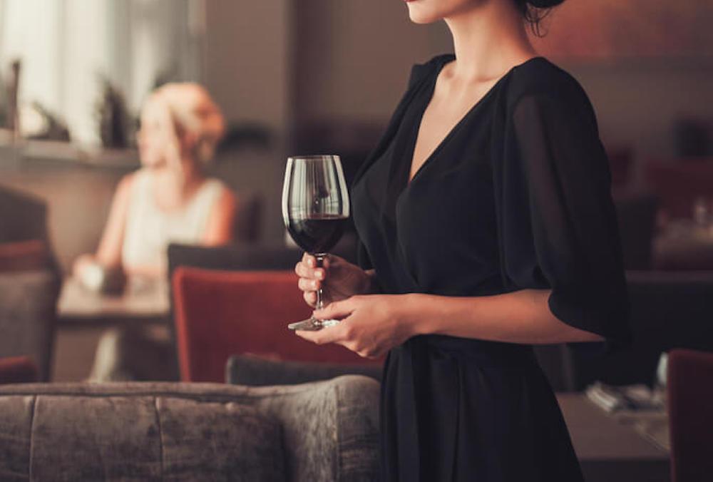 ブラックのドレスを着てワインを持っている女性