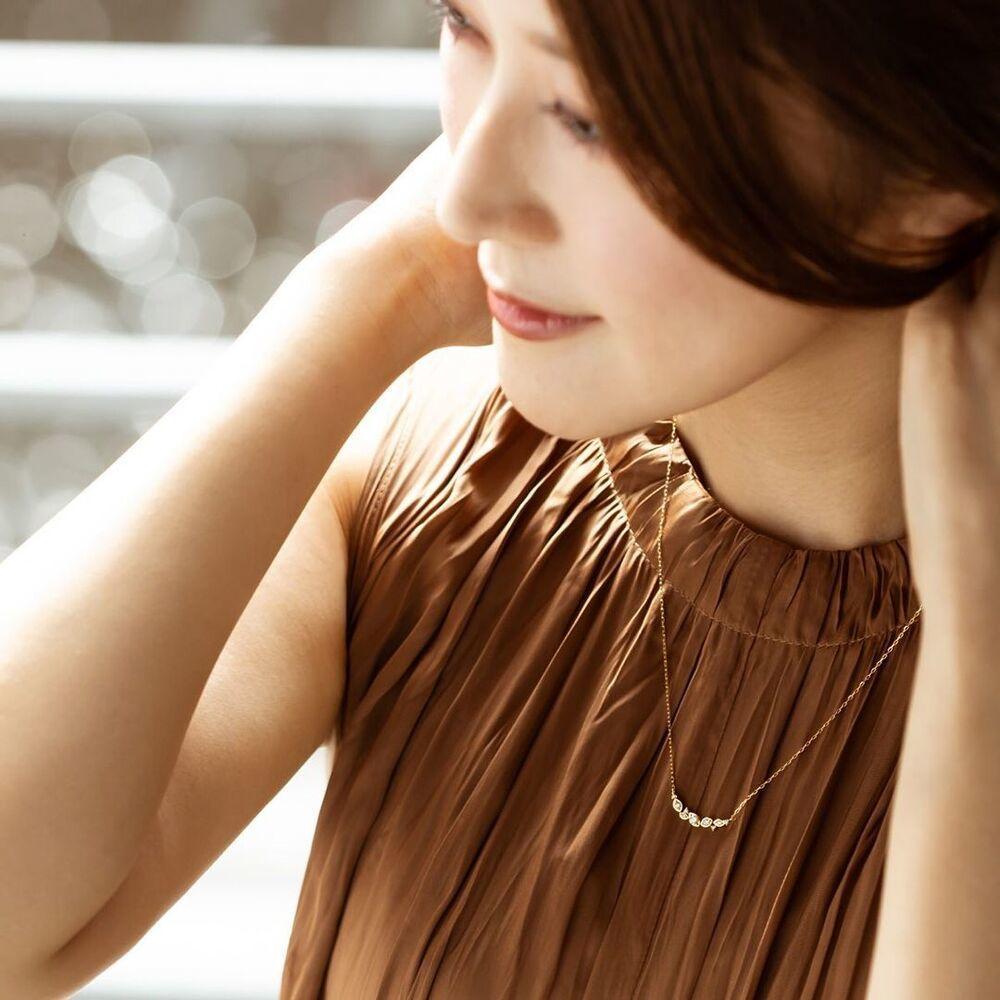 ブラウンの服に4℃のゴールドネックレス合わせる女性