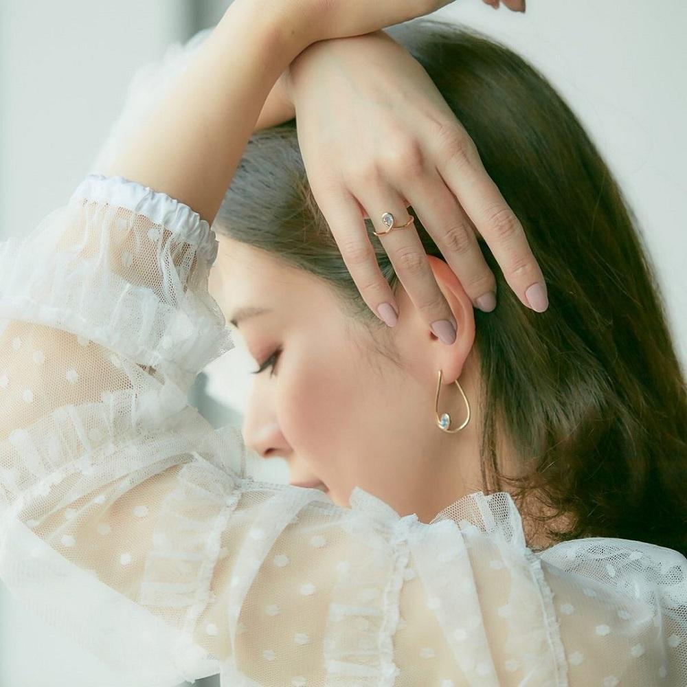 4℃の指輪とピアスをする女性