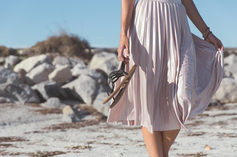 フェミニンなファッションで砂浜を歩く女性
