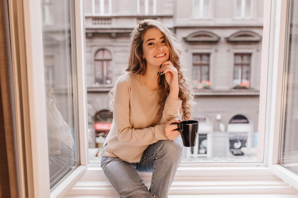 窓際でコーヒーを飲む女性
