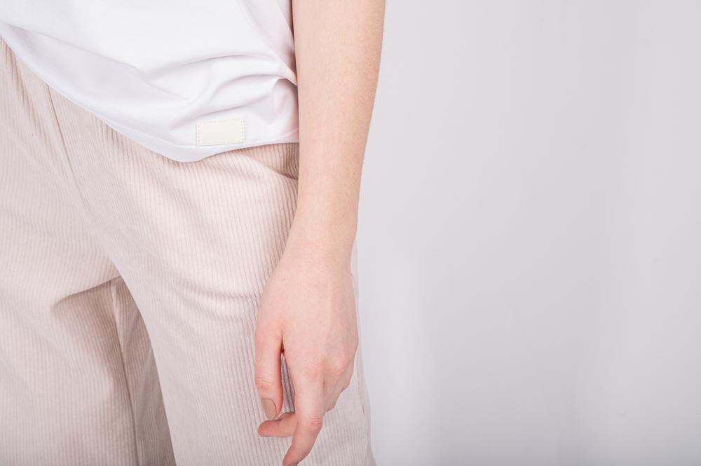 ベージュのボトムスを履いている女性