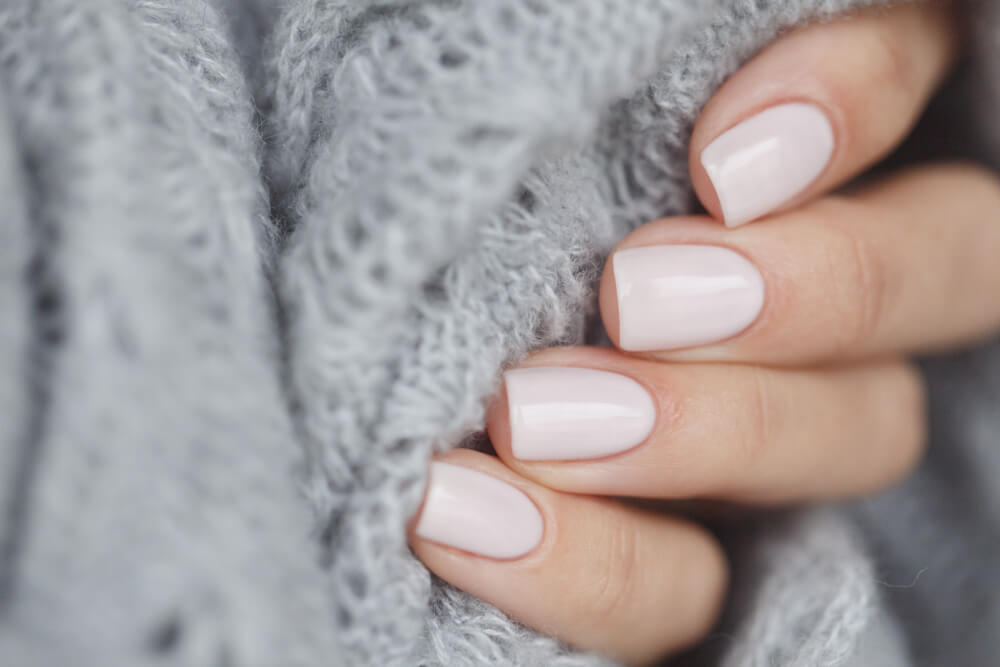 白いネイルを塗りグレーのニットを握る女性の手