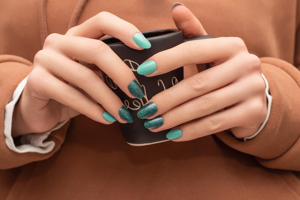 異なる質感のネイルを塗った女性の手