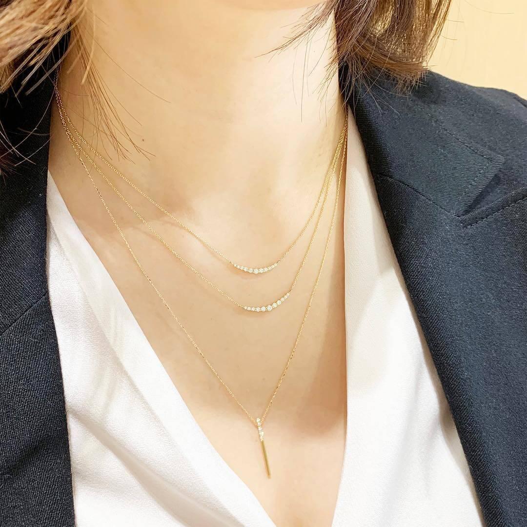 4℃の3本のゴールドネックレスを重ね着けする女性