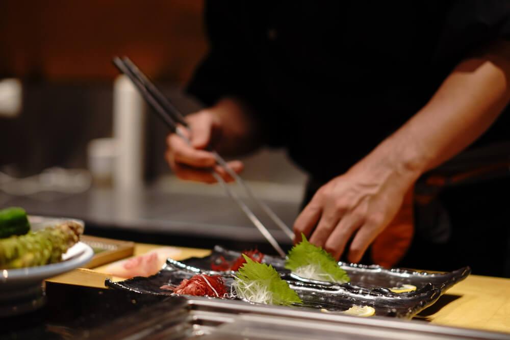 皿に食材を盛りつける料理人