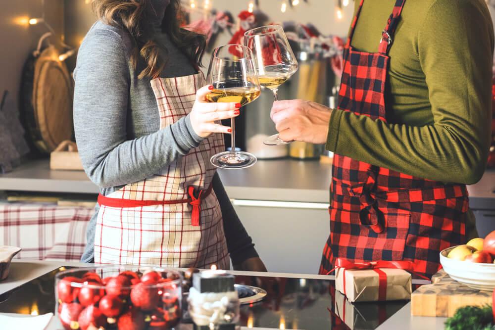 料理をしながらお酒を飲むカップル