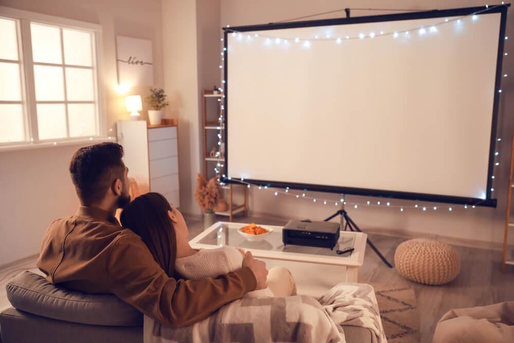 部屋で映画を見るカップル
