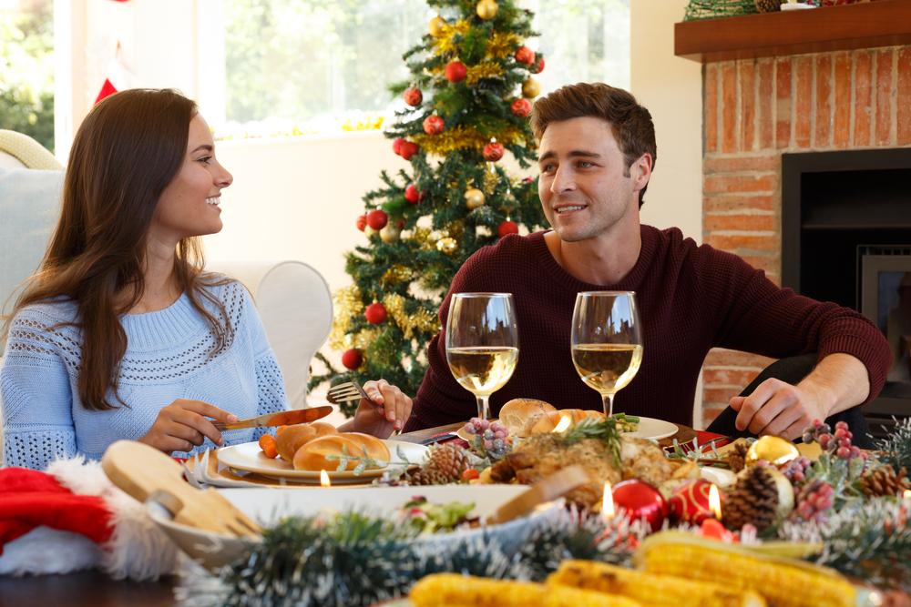 家でクリスマスディナーを楽しむカップル