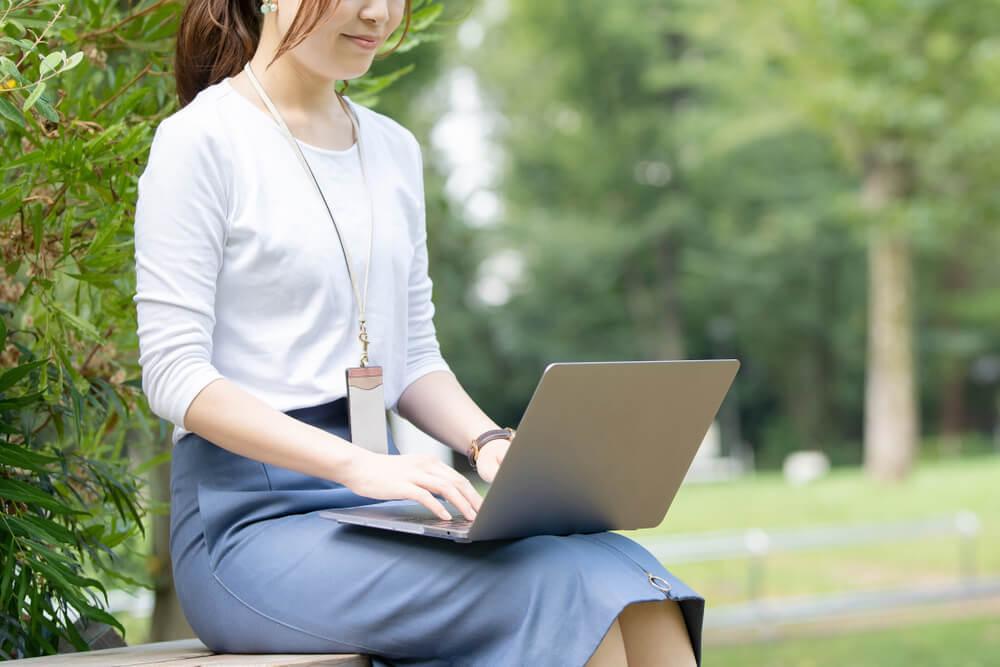 屋外でパソコンを使う女性
