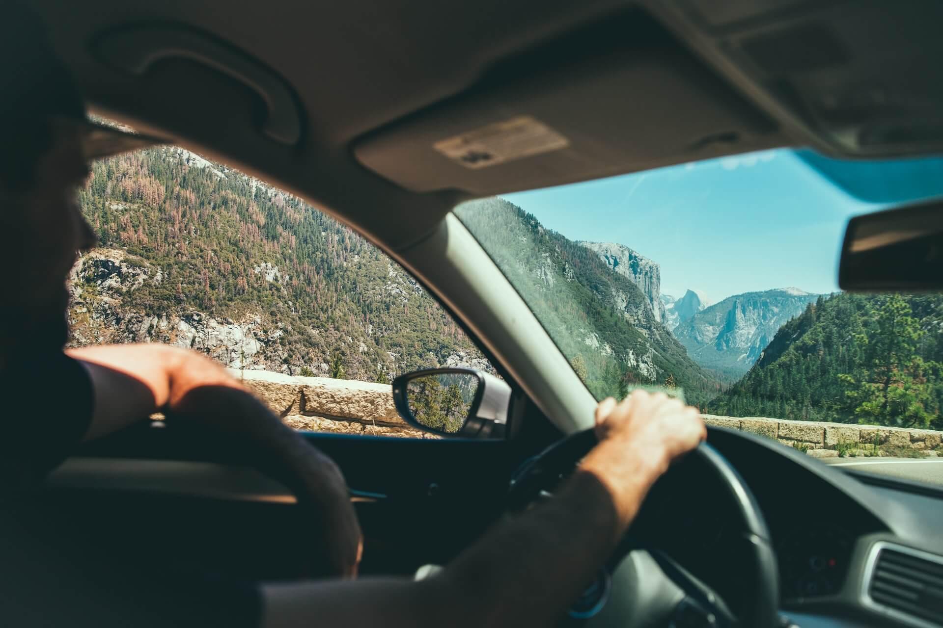 窓から見える景色と車のハンドルを握る手