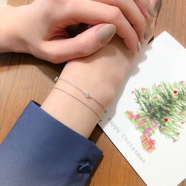 メッセージカードとブレスレットを身に着けた女性の手